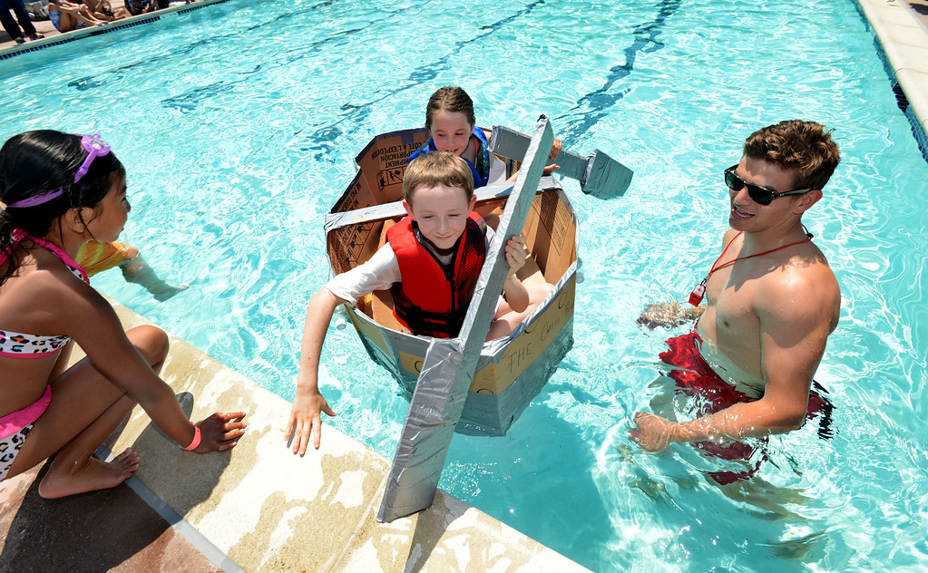 """. Toby Radding, left, and his sister Taylor Radding, 8, of Lafayette, make it across a pool in their watercraft named \""""The Cheese Boat!!!\"""" made of only cardboard, recyclables and duct tape during the Derby Day boat race held at Pleasant Hill Aquatic Park in Pleasant Hill, Calif., on Friday, July 19, 2013. (Doug Duran/Bay Area News Group)"""