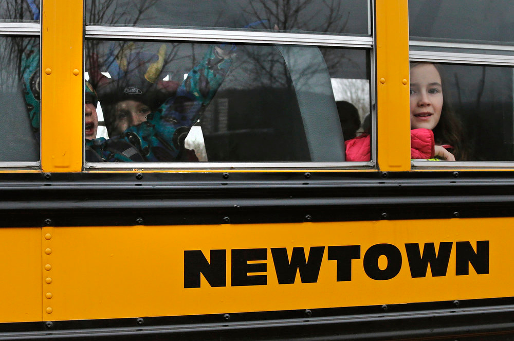 Description of . Schoolchildren look out the window of their bus as they head back to school in Newtown, Conn., Tuesday, Dec. 18, 2012. Classes resume Tuesday for Newtown schools except those at Sandy Hook. Buses ferrying students to schools were festooned with large green and white ribbons on the front grills, the colors of Sandy Hook. At Newtown High School, students in sweatshirts and jackets, many wearing headphones, betrayed mixed emotions.  Adam Lanza walked into Sandy Hook Elementary School in Newtown,  Friday and opened fire, killing 26 people, including 20 children, before killing himself. (AP Photo/Charles Krupa)
