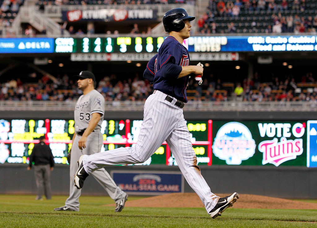 . Minnesota Twins\' Justin Morneau scores on Trevor Plouffe\'s  two-run double against Chicago White Sox starting pitcher Hector Santiago, left, during the third inning of a baseball game, Monday, May 13, 2013, in Minneapolis. (AP Photo/Genevieve Ross)