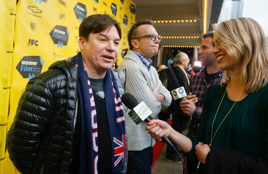 """. Mike Myers, left, and Tom Arnold, center, arrive on the red carpet for a screening of their new film \""""Supermensch\"""" during the SXSW Film Festival on Sunday, March 9, 2014 in Austin, Texas. (Photo by Jack Plunkett/Invision/AP)"""