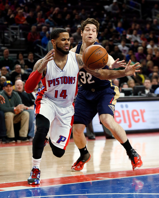 . Detroit Pistons guard D.J. Augustin (14) drives on New Orleans Pelicans guard Jimmer Fredette (32) during the first half of an NBA basketball game in Auburn Hills, Mich., Wednesday, Jan. 14, 2015. (AP Photo/Paul Sancya)