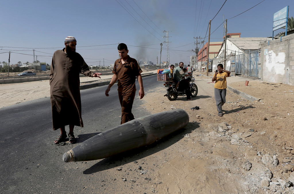 . Palestinian onlookers and motorists pause to inspect a bomb from the Israeli military lying unexploded on the main road in Deir el-Balah in the central Gaza Strip, Friday, Aug. 1, 2014. (AP Photo/Adel Hana)