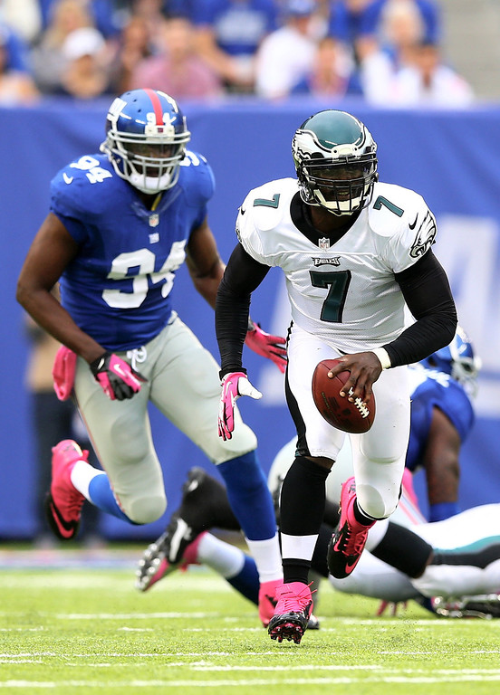 . Michael Vick #7 of the Philadelphia Eagles scrambles as  Mathias Kiwanuka #94 of the New York Giants defends at MetLife Stadium on October 6, 2013 in East Rutherford, New Jersey.  (Photo by Elsa/Getty Images)