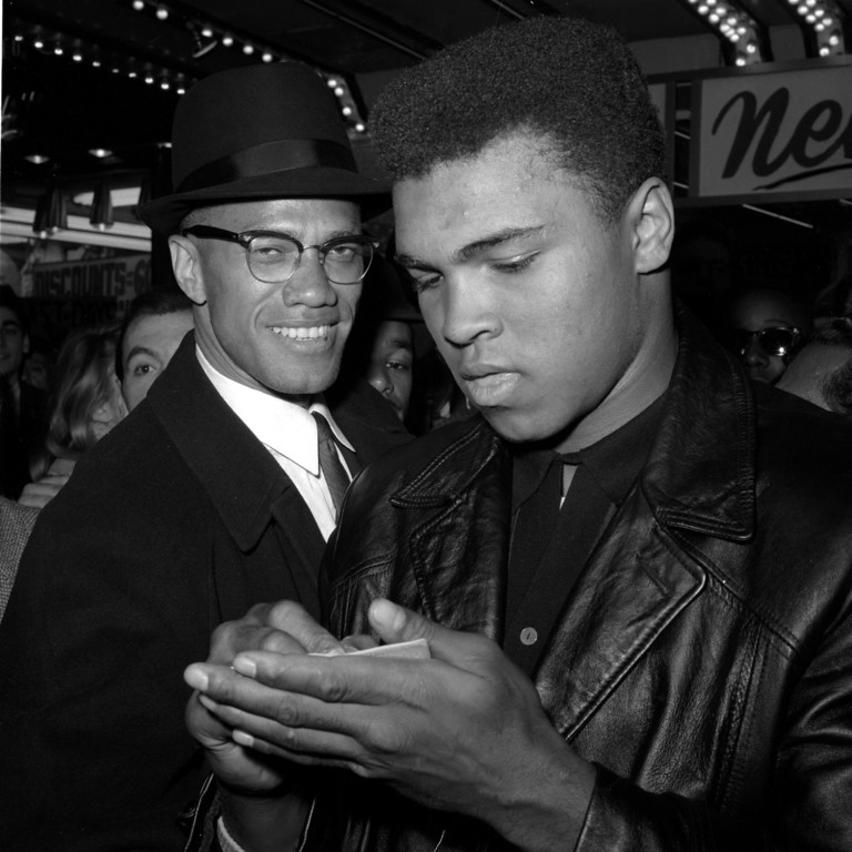. World Heavyweight Boxing Champion, Muhammad Ali, right, is shown with Black Muslim Leader, Malcolm X, outside the Trans-Lux Newsreel Theater on Broadway at 49th Street, New York City, March 1, 1964.  They had just watched a screening of films on Ali\'s title fight with Sonny Liston in Miami Beach, Feb. 25.  (AP Photo)