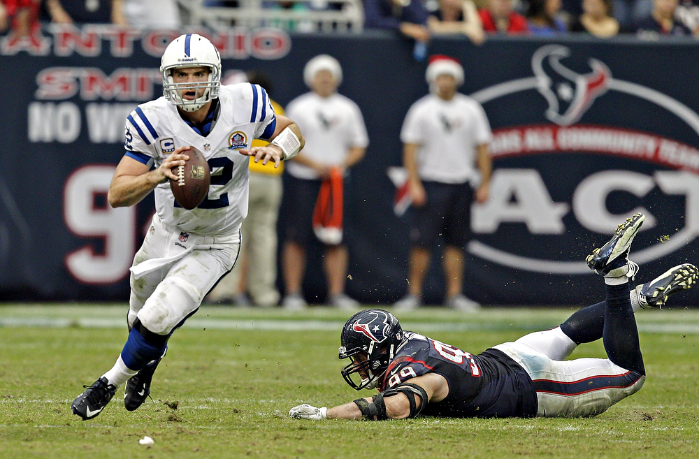 . Andrew Luck #12 of the Indianapolis Colts avoids the tackle by J.J. Watt #99 of the Houston Texans in the second half at Reliant Stadium on December 16, 2012 in Houston, Texas. Texans win 29-17 to clinch the AFC South. (Photo by Bob Levey/Getty Images)