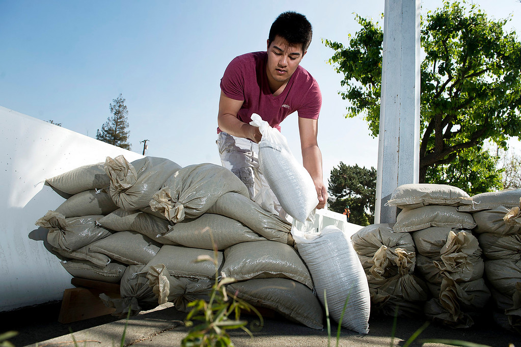 . Chris Romero, 17, helps his neighbors stack sandbags along the 800 block of Rainbow Drive in Glendora on Tuesday, Feb. 25, 2014. The city of Glendora is preparing for two major rainstorms that will hit the region this week that potentially will cause mudslides in the area devastated by the Colby Fire. (Photo by Watchara Phomicinda/ San Gabriel Valley)