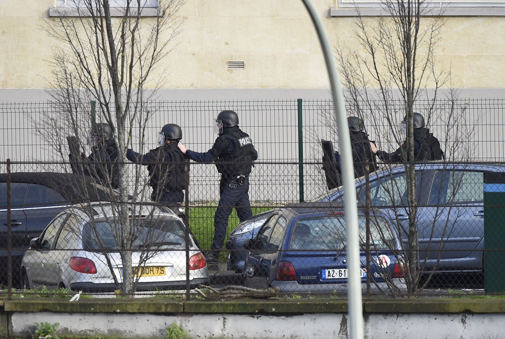 . French police special forces walk in line behind their protection shields on January 9, 2015 in Saint-Mande, near Porte de Vincennes, eastern Paris, after at least one person was injured when a gunman opened fire at a kosher grocery store on January 9, 2015 and took at least five people hostage, sources told AFP. The attacker was suspected of being the same gunman who killed a policewoman in a shooting in Montrouge in southern Paris on January 8. AFP PHOTO / MARTIN BUREAU/AFP/Getty Images