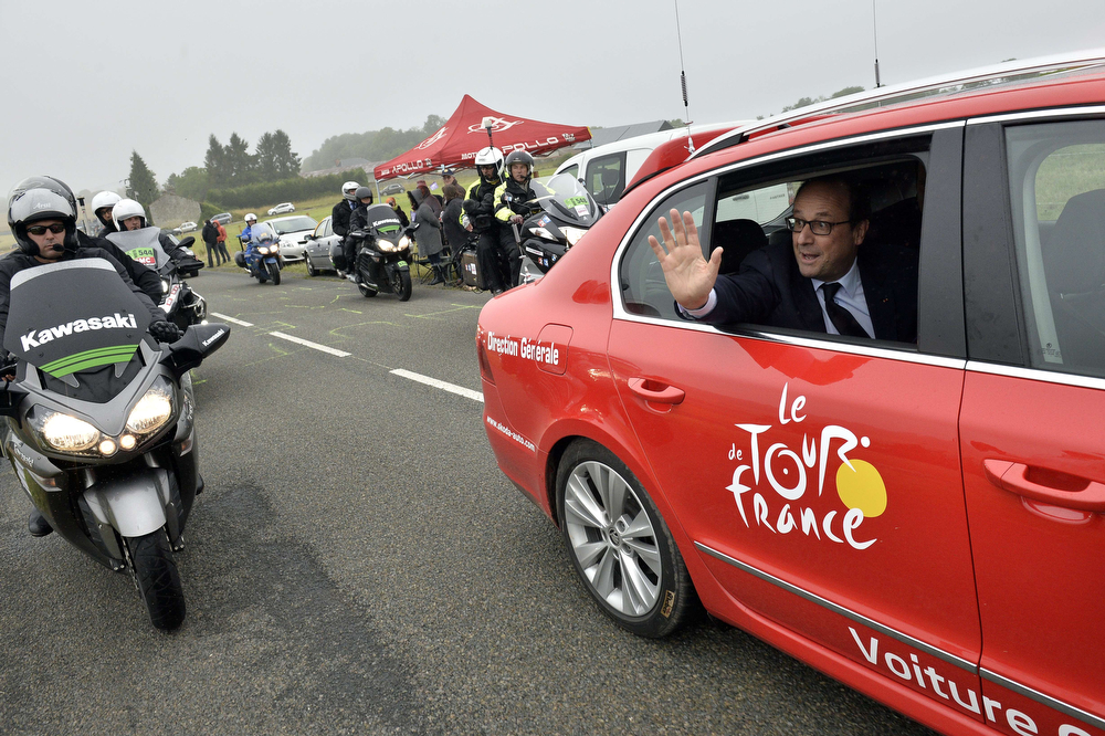 . French President Francois Hollande waves to the crowd from an official car as part of his visit during the 194 km sixth stage of the 101st edition of the Tour de France cycling race on July 10, 2014 between Arras and Reims, northern France.  (JEFF PACHOUD/AFP/Getty Images)