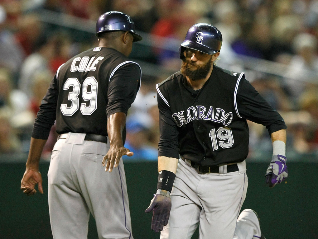 . Colorado Rockies\' Charlie Blackmon (19) celebrates with third base coach Stu Cole (39) after hitting a solo home run in the ninth inning of a baseball game against the Arizona Diamondbacks, Saturday, Aug. 30, 2014, in Phoenix. (AP Photo/Rick Scuteri)