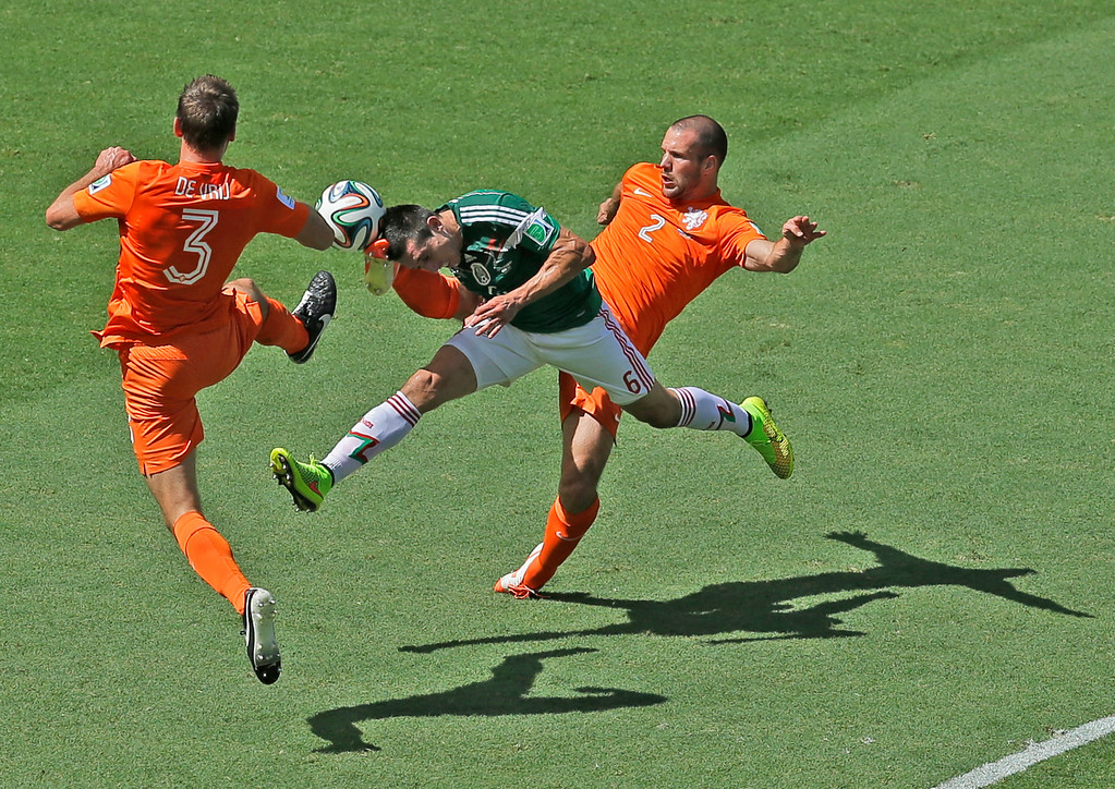 . Mexico\'s Hector Herrera, center, challenges for the ball with Netherlands\' Stefan de Vrij, left, and Ron Vlaar during the World Cup round of 16 soccer match between the Netherlands and Mexico at the Arena Castelao in Fortaleza, Brazil, Sunday, June 29, 2014. (AP Photo/Themba Hadebe)