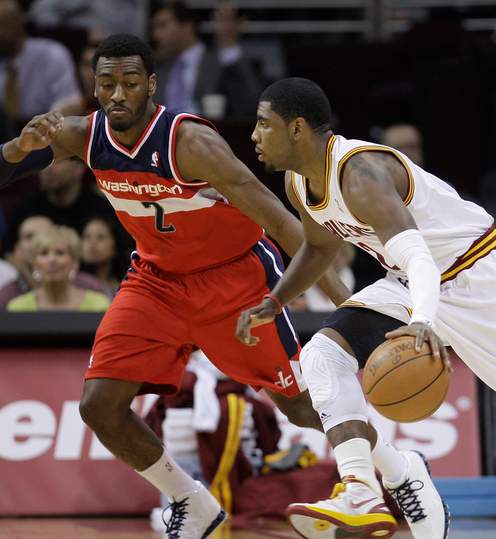 . Cleveland Cavaliers\' Kyrie Irving, right, drives past Washington Wizards\' John Wall in the first quarter in an NBA basketball game on Wednesday, April 25, 2012, in Cleveland. (AP Photo/Tony Dejak)