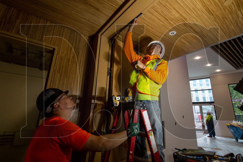 Josh Madsen, left, and Sebastian McGaw, both union electricians with Affordable Electric, run power to a door operator at the Oregon Convention Center. The $39 million renovation is being carried out by minority-owned Colas Construction. (Sam Tenney/DJC)