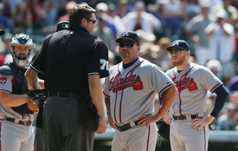 . Atlanta Braves manager Fredi Gonzalez, second from right, looks on as home plate umpire Jordan Baker, front left, tries to restore order after Colorado Rockies\' batter Corey Dickerson was hit by a pitch which triggered the ejection of Rockies manager Walt Weiss in the eighth inning of the Rockies\' 10-3 victory in a baseball game in Denver, Thursday, June 12, 2014. (AP Photo/David Zalubowski)
