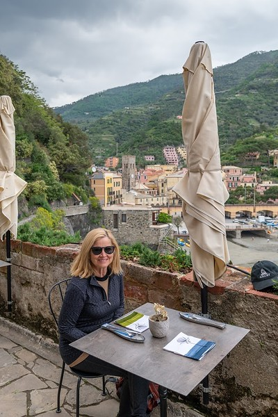 woman at table with folded up umbrella on a trip to Cinque Terre