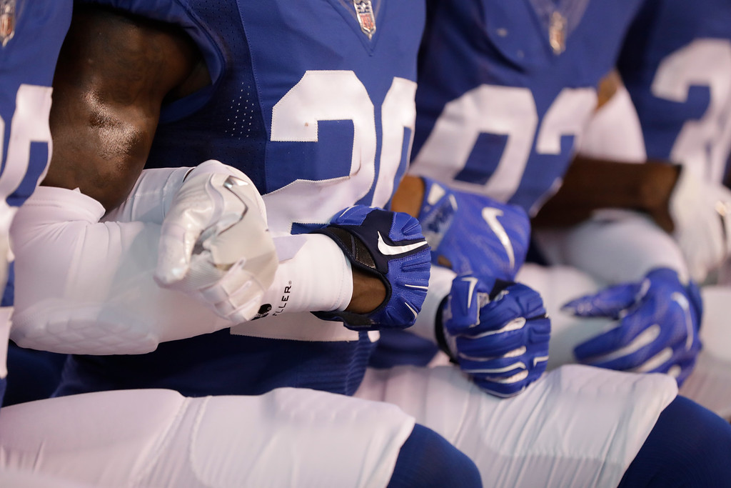 . Members of the Indianapolis Colts lock arms as they take a knee during the Nation Anthem before an NFL football game against the Cleveland Browns in Indianapolis, Sunday, Sept. 24, 2017. (AP Photo/Darron Cummings)