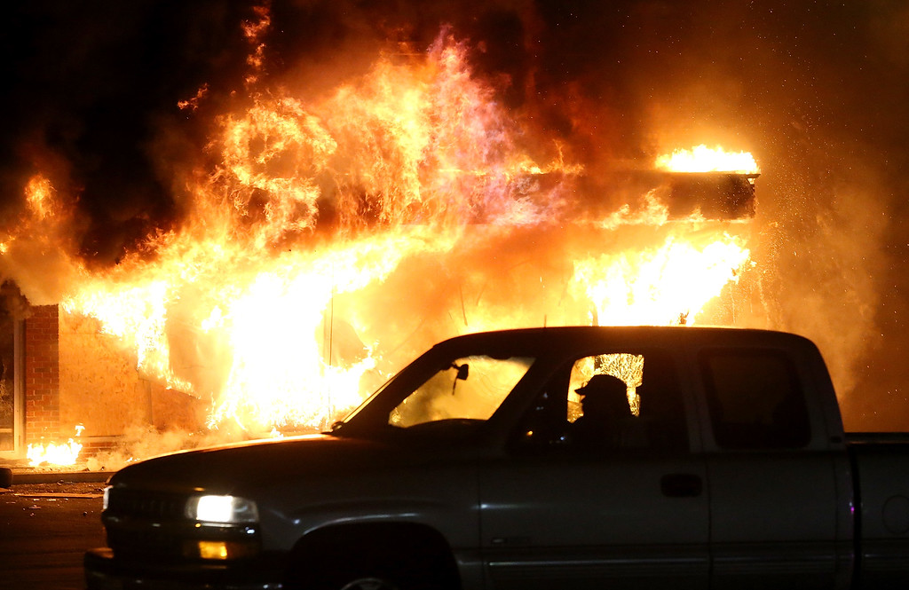 . A car drives by a burning building during a demonstration on November 25, 2014 in Ferguson, Missouri. Ferguson has been struggling to return to normal after Brown, an 18-year-old black man, was killed by Darren Wilson, a white Ferguson police officer, on August 9. His death has sparked months of sometimes violent protests in Ferguson. A grand jury today declined to indict officer Wilson.  (Photo by Justin Sullivan/Getty Images)