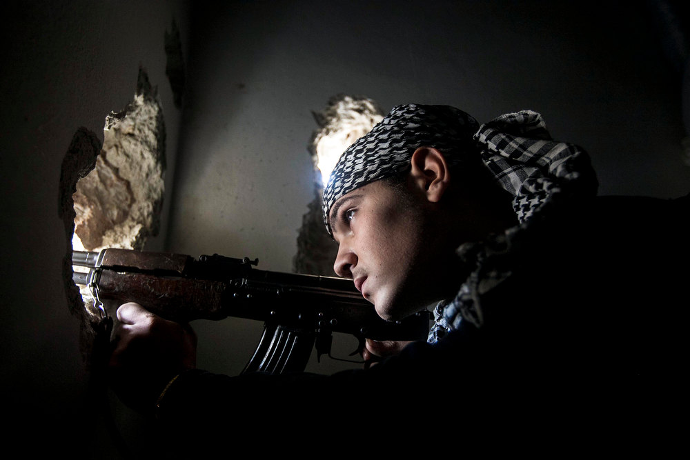 Description of . In this Monday, Dec. 10, 2012 photo, a Free Syrian Army fighter aims his weapon during heavy clashes with government forces in Aleppo, Syria. (AP Photo/Narciso Contreras)