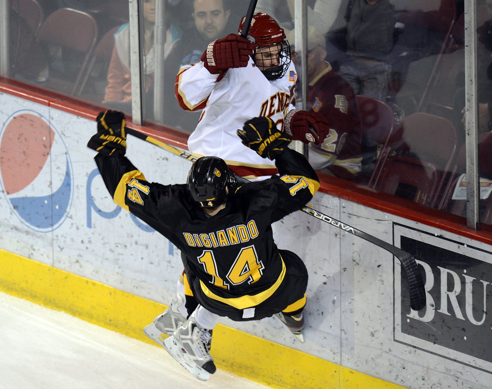 . DENVER, CO. - FEBRUARY 08: Nolan Zajac of University of Denver #8 checks Jordan DiGiando of  Colorado College #14 in the 1st period of the game February 8, 2013 at Magness Arena in Denver, Colorado. (Photo By Hyoung Chang/The Denver Post)