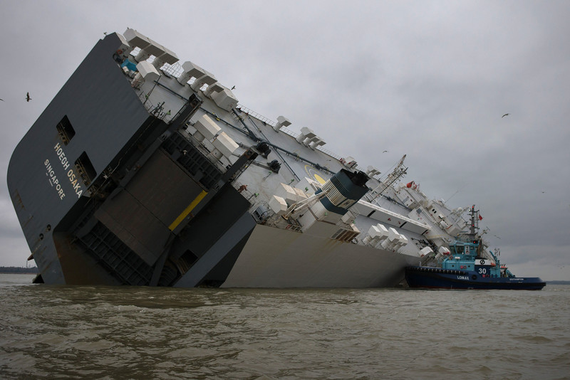 . Salvage tugs stay close to the stricken vessel \'Hoegh Osaka\' after it ran aground on a sand bank in the Solent on January 5, 2015 in Cowes, England.  According to the owners of the Hoegh Osaka, the 52,000 ton cargo ship which is carrying 1,400 cars, some of which are thought to include Rolls Royces and Bentleys and is now stricken off the Isle of Wight, was deliberately grounded to prevent it from capsizing after it began listing as it left port. The ship became grounded on Bramble Bank in the Solent on Saturday night, forcing emergency services to rescue all 25 crew members on board.  (Photo by Matt Cardy/Getty Images)