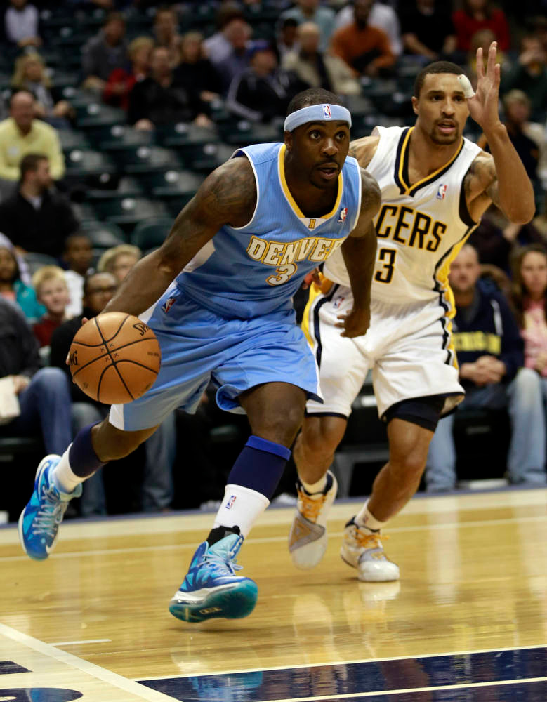 . Denver Nuggets guard Ty Lawson (L) drives to the basket passing Indiana Pacers guard George Hill (3) during the first quarter of an NBA basketball game in Indianapolis, Indiana December 7, 2012.  REUTERS/Brent Smith