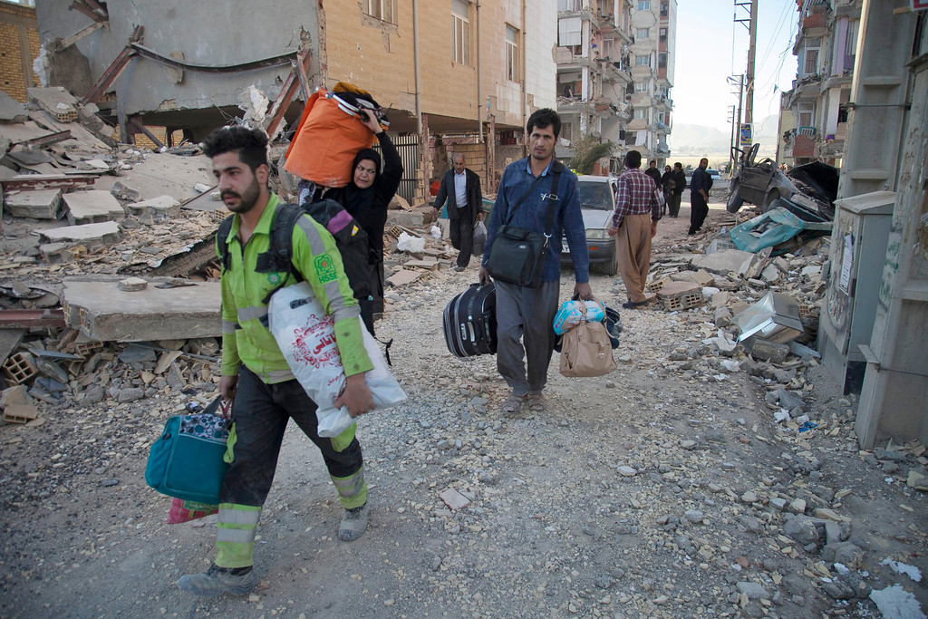 . In this photo provided by Tasnim News Agency, people carry their belongings in Sarpol-e-Zahab, western Iran, Monday, Nov. 13, 2017. Authorities reported that a powerful 7.3 magnitude earthquake struck the Iraq-Iran border region on Monday and killed more than three hundred people in both countries, sent people fleeing their homes into the night and was felt as far west as the Mediterranean coast. (Farzad Menati/Tasnim News Agency via AP)