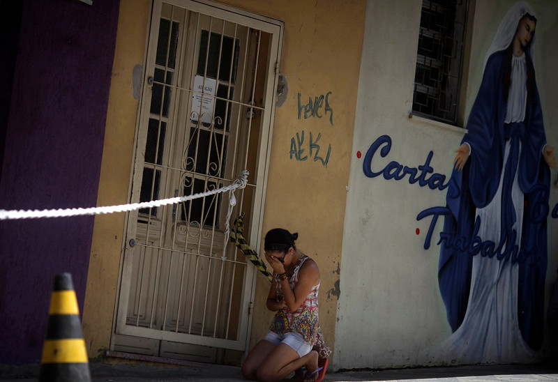 . A woman kneels next to the Boate Kiss nightclub, in the southern city of Santa Maria, 187 miles (301 km) west of the state capital Porto Alegre, January 29, 2013. Brazilian police investigating a nightclub fire that killed 231 people detained on Monday the owners of the club and two band members whose pyrotechnics show authorities say triggered the blaze. REUTERS/ Ricardo Moraes
