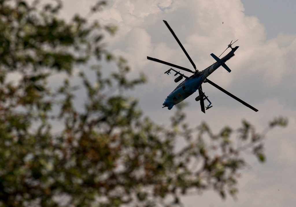 . A Ukrainian helicopter gunship flies above areas where pro-Russian militias have taken positions around the airport, outside Donetsk, Ukraine, on Monday, May 26, 2014. Ukraine\'s military launched air strikes Monday against separatists who had taken over the airport in the eastern capital of Donetsk in what appeared to be the most visible operation of the Ukrainian troops since they started a crackdown on insurgents last month. (AP Photo/Vadim Ghirda)