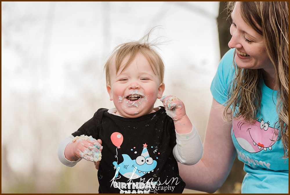 Photo of boy smiling with cake on face and mom smiling at him
