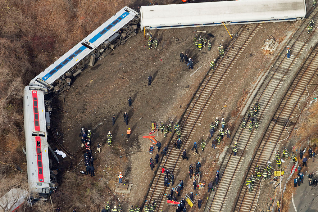 . Emergency rescue personnel work the scene of a Metro-North passenger train derailment in the Bronx borough of New York, Sunday, Dec. 1, 2013. The train derailed on a curved section of track on Sunday morning, coming to rest just inches from the water and causing multiple fatalities and dozens of injuries, authorities said. Metropolitan Transportation Authority police say the train derailed near the Spuyten Duyvil station. (AP Photo/Mark Lennihan)