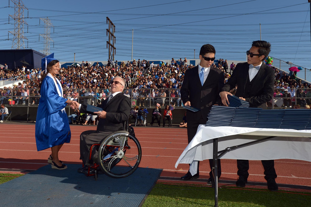 . Derek Inouye, middle, and Yutaro Shigeta, right, help TUSD Borad of Education Clerk Mark Steffen present diplomas. The 2013 North High School commencement ceremonies take place on the school\'s football field in Torrance Wednesday afternoon.