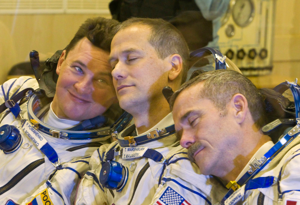 Description of . The International Space Station (ISS) crew members, from left: Russian cosmonaut Roman Romanenko, U.S. astronaut Thomas Marshburn and Canadian astronaut Chris Hadfield joke during their talk with relatives after putting on their space suits at the Baikonur cosmodrome  Kazakhstan Wednesday, Dec. 19, 2012.  (AP Photo/ Shamil Zhumatov, pool)