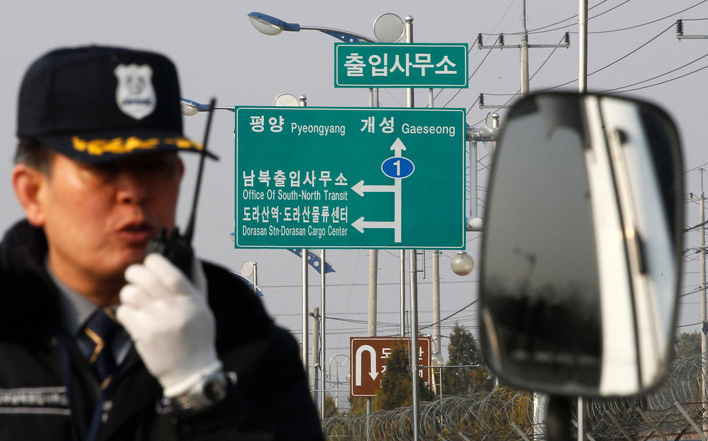 . A South Korean security guard works to turn back vehicles as they were refused to enter to Kaesong, North Korea, at the customs, immigration and quarantine office in Paju, South Korea, near the border village of Panmunjom, Thursday, April 4, 2013. North Korea on Wednesday barred South Korean workers from entering a jointly run factory park just over the heavily armed border in the North, officials in Seoul said, a day after Pyongyang announced it would restart its long-shuttered plutonium reactor and increase production of nuclear weapons material. (AP Photo/Ahn Young-joon)