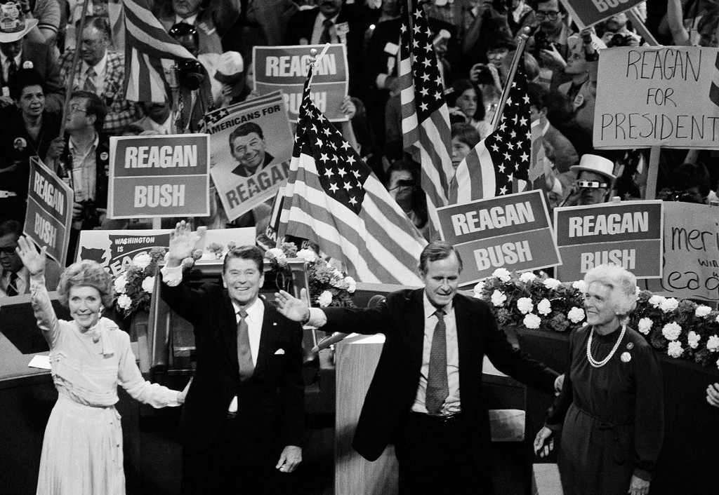 . Republican presidential candidate Ronald Reagan and his running mate George Bush are shown on the podium of Joe Louis Arena in Detroit, July 17, 1980 as the final curtain draws near on the 1980 Republican National Convention. Nancy Reagan stands left, Barbara Bush, right. (AP Photo)