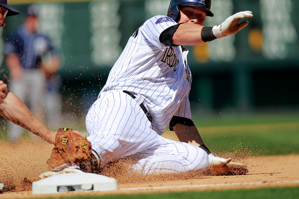 . Colorado Rockies\' Corey Dickerson Is tagged out at third by San Diego Padres\' Chase Headley after driving in Dexter Fowler with a double during the eighth inning of a baseball game Wednesday, Aug. 14, 2013, in Denver. (AP Photo/Barry Gutierrez)