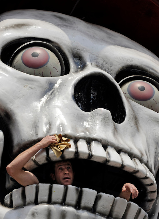 . A man cleans the giant skull of a ghost train at the opening of the 575. Cranger Fair in Herne, western Germany, Friday, Aug. 6, 2010. What once started as a horse market in the 15th century has become one of Germany\'s biggest fun fairs with 500 exhibitors and about four million visitors within ten days. (AP Photo/Martin Meissner)