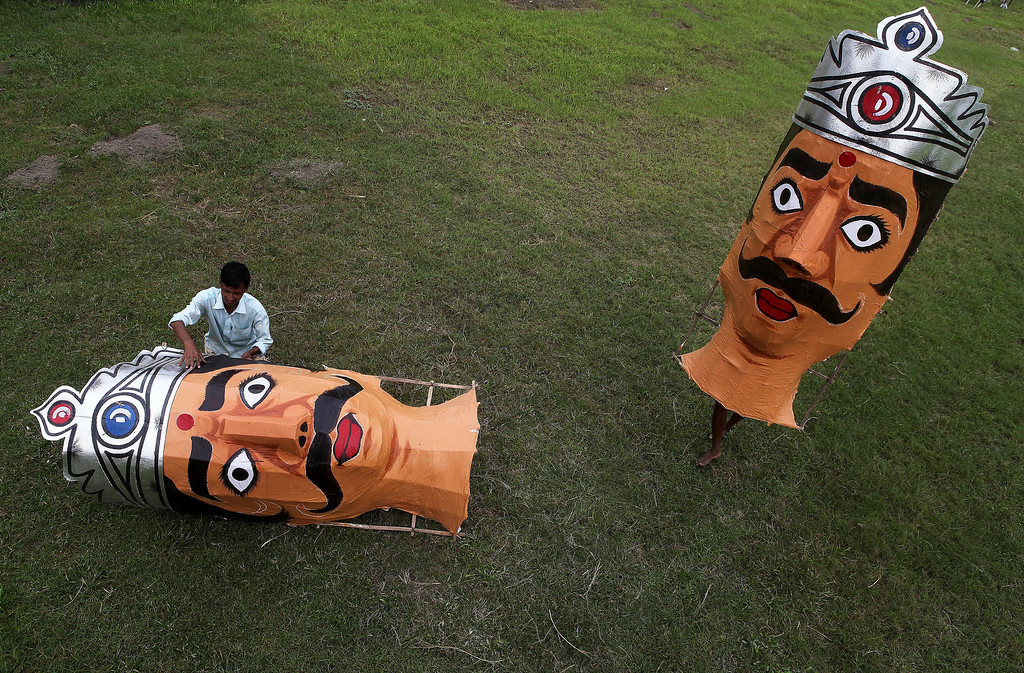 . Bubul Haque, an Indian artist prepares an effigy of the demon king Ravana as another artist carries another effigy during preparations for the Dussehra festival celebrations, in Gauhati, India, Sunday, Oct. 13 2013.  The festival commemorates the victory of Hindu god Rama over demon king Ravana, and a celebration of the victory of good over evil. (AP Photo/Anupam Nath)