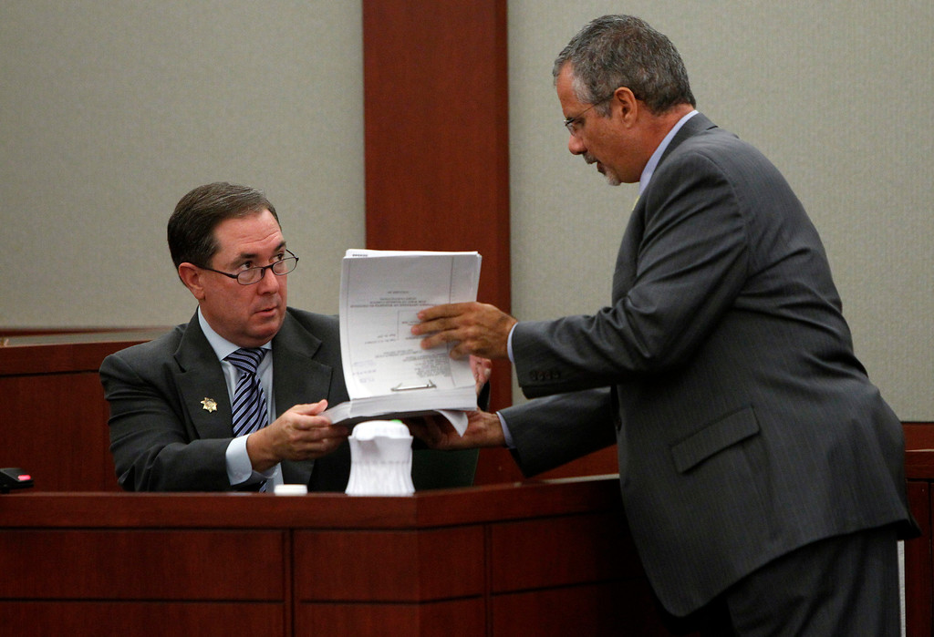 . Former Clark County District Attorney and O.J. Simpson trial prosecutor David Roger, left, hands documents back to defense attorney Ozzie Fumo at an evidentiary hearing for Simpson in Clark County District Court on Tuesday, May 14, 2013 in Las Vegas.  The hearing is aimed at proving Simpson\'s trial lawyer, Yale Galanter, had conflicted interests and shouldn\'t have handled Simpson\'s case. Simpson is serving nine to 33 years in prison for his 2008 conviction in the armed robbery of two sports memorabilia dealers in a Las Vegas hotel room. (AP Photo/Steve Marcus, Pool)