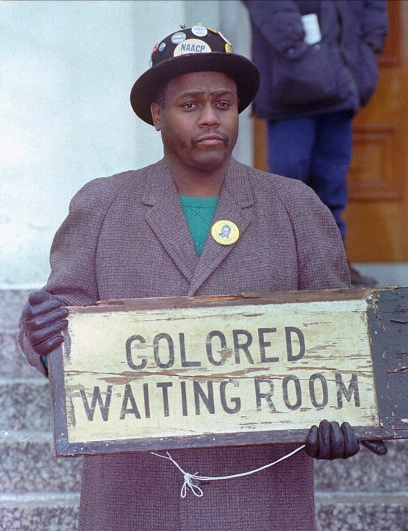 . Calvin Riley, of St. Louis, holds a sign during the 27th annual march and celebration for Dr. Martin Luther King, Jr. Monday, Jan. 19, 1998, in St. Louis. Riley, who collects pre-1940 black memorabilia, found this sign in a small town in Tennesse, and said the 1930\'s era sign probably hung in a bus or train station.(AP Photo/Leon Algee)