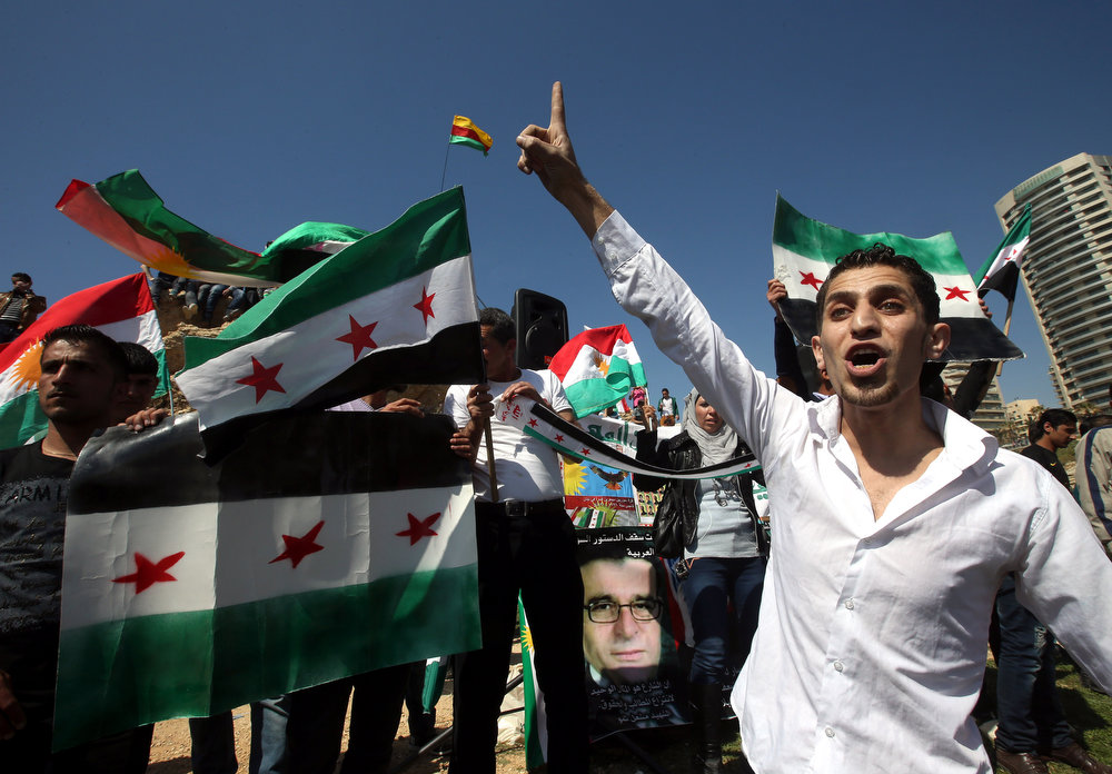 . A Syrian Kurdish man who lives in Lebanon and is opposed to Syrian President Bashar Assad, shouts slogans against the Syrian regime as others hold Syrian revolutionary flags, as they celebrate the Nowruz day in Beirut, Lebanon, Thursday March 21, 2013.  Nowruz, the Farsi-language word for \'new year\', is an ancient Persian festival, celebrated on the first day of spring in central Asian Republics, Afghanistan, Iran, Iraq and Turkey. (AP Photo/Hussein Malla)