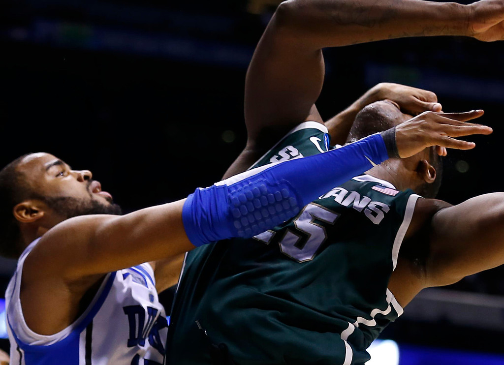 . Michigan State Spartans forward Derrick Nix (R) is fouled by Duke Blue Devils forward Josh Hairston during their Midwest Regional NCAA men\'s basketball game in Indianapolis, Indiana, March 29, 2013. REUTERS/Jeff Haynes