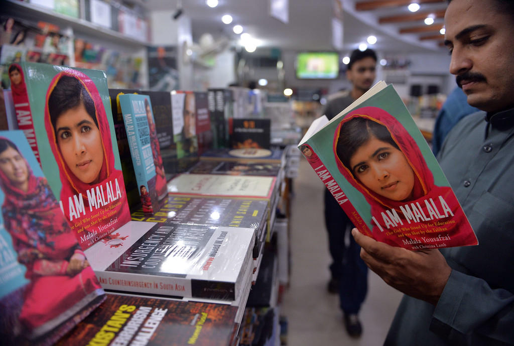 """. A Pakistani customer reads the autobiography of Malala Yousafzai at a bookstore in Islamabad on October 10, 2014. Malala Yousafzai was hailed as the \""""pride of Pakistan\"""" by Prime Minister Nawaz Sharif for winning the Nobel Peace Prize, as a former fellow pupil said the award was a victory for every girl in the country. Political leaders and activists alike rallied around Malala, the youngest ever Nobel laureate, expressing their support for the education campaigner who moved to Great Britain after being shot in the head by Taliban militants two years ago. AFP PHOTO/ Aamir QURESHI/AFP/Getty Images"""