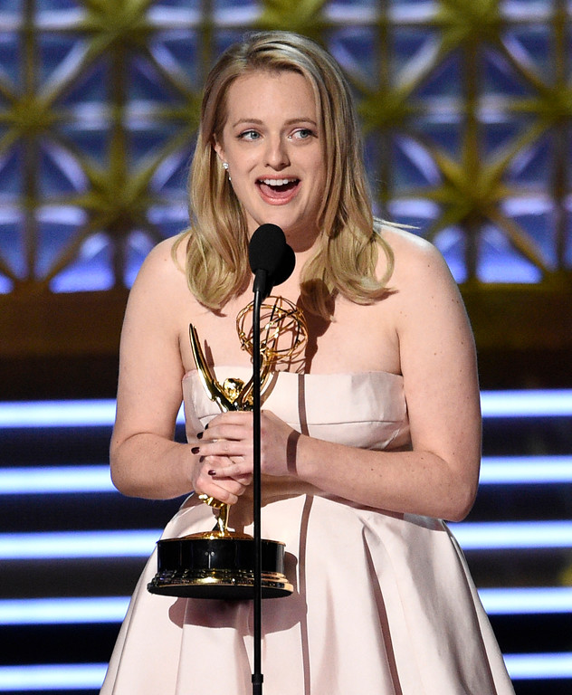 ". Elisabeth Moss accepts the award for outstanding lead actress in a drama series for ""The Handmaid\'s Tale\"" at the 69th Primetime Emmy Awards on Sunday, Sept. 17, 2017, at the Microsoft Theater in Los Angeles. (Photo by Chris Pizzello/Invision/AP)"