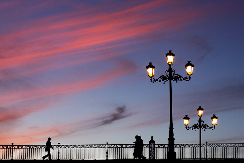 People on Triana Bridge at dusk
