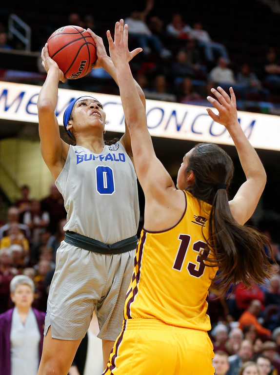 . Buffalo forward Summer Hemphill,left, shoots over Central Michigan forward Reyna Frost during the first half of an NCAA college basketball game in the championship of the Mid-American Conference tournament Saturday, March 10, 2018, in Cleveland. Central Michigan won 96-91. (AP Photo/Ron Schwane)