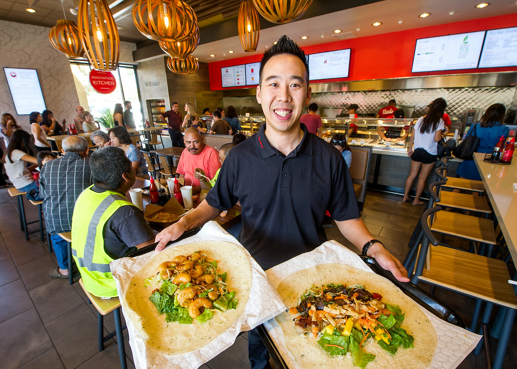 . Jih Cheng, General Manager Lead Panda Innovation Kitchen holding, Sweet and Crispy Wrap, left, containing honey walnut shrimp, papaya slaw with crispy wontons, Manager Favorite, containing Brown Rice, salad, eggplant, basil, grilled chicken wrap atPanda Express, located at 3867 East Foothill Boulevard in Pasadena Thursday, August 21, 2014.  This unique restaurant is the  location of the chain\'s Innovation Kitchen. Here, consumers can try test cuisine and also contribute their own ideas for new dishes.  (Photo by Walt Mancini/Pasadena Star-News)