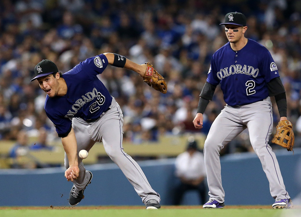 . Third baseman Nolan Arenado #28 of the Colorado Rockies tries to barehand the ball but can\'t hang on as Yasiel Puig #66 of the Los Angeles Dodgers gets an infield single in the fourth inning as shortstop Troy Tulowitzki #2 looks on at Dodger Stadium on July 11, 2013 in Los Angeles, California.  (Photo by Stephen Dunn/Getty Images)