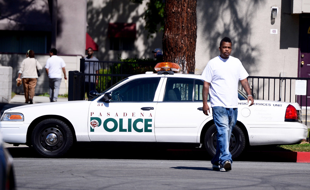 . People walk in and out of Kings Village in Pasadena as Pasadena Police investigate an officer involved shooting at the Pasadena apartment complex Friday, October 11, 2013. (Photo by Sarah Reingewirtz/Pasadena-Star News)