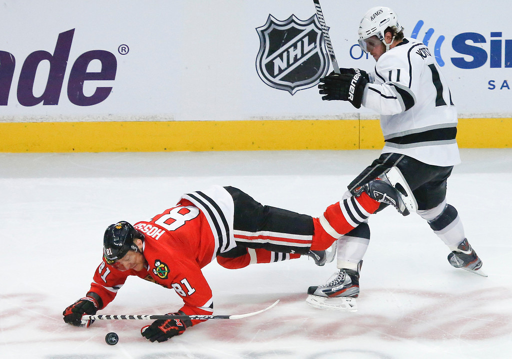 . Chicago Blackhawks right wing Marian Hossa (81) trips over Los Angeles Kings center Anze Kopitar (11) during the second period in Game 2 of the NHL hockey Stanley Cup Western Conference finals Sunday, June 2, 2013 in Chicago. (AP Photo/Charles Rex Arbogast)