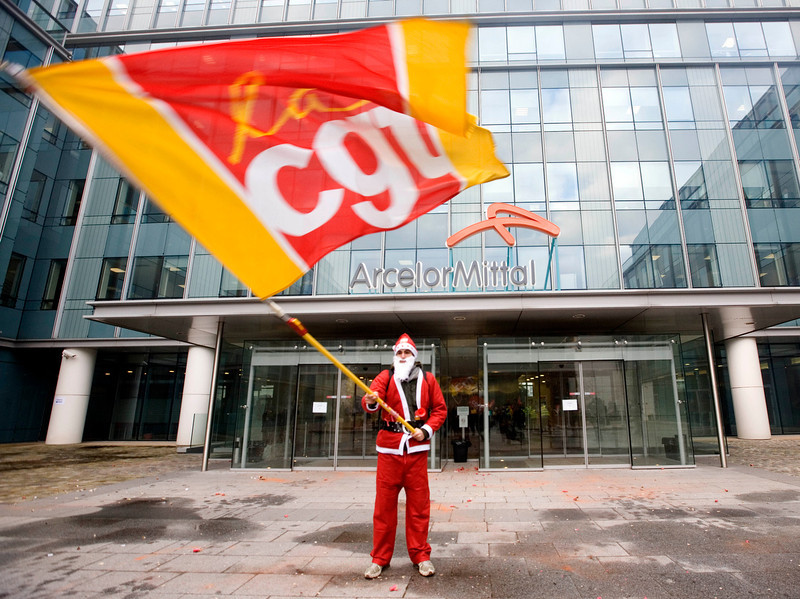 . A steel worker of ArcelorMittal dressed as Santa Claus, waves his union flag as he demonstrates against job cuts outside the company\'s French headquarters outside Paris, Wednesday Dec. 10, 2008. The Luxembourg-based ArcelorMittal, the world\'s largest steel maker, said last week it is looking to cut 9,000 jobs through voluntary agreements, shedding around 3 percent of its global workforce in response to the economic downturn. ArcelorMittal has over 326,000 employees in more than 60 countries. On flag reads: CGT for union Confederation General du Travail (Working General Confederation). (AP Photo/Jacques Brinon)
