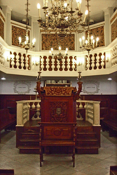 58-Looking west over the bimah and back to the entry to the Conegliano Synagogue and the women's balcony. In Italy, this bimah was located at the west end of the hall, opposite the Torah Ark at the Eastern wall. This bimah is now almost in the middle of the hall.